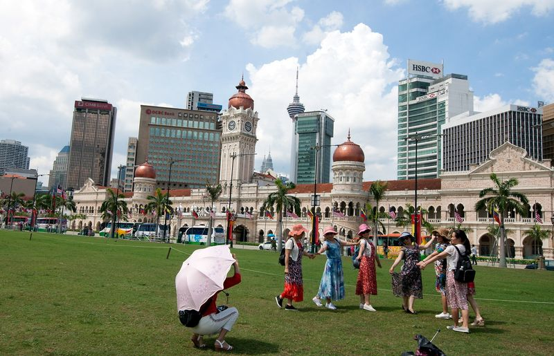 Tourists take pictures against the backdrop of the Sultan Abdul Samad Building at Dataran Merdeka in Kuala Lumpur June 25, 2017. — Bernama pic
