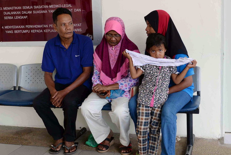 The victim's father Zaini Saad (left) wait with family members at the Forensics Department in Hospital Sultanah Bahiyah. —  Bernama pic
