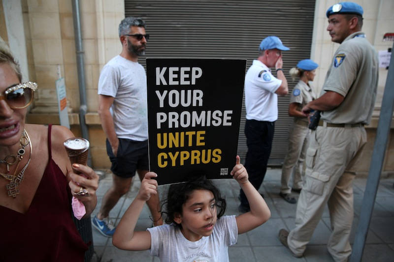 A girl holds a placard during a demonstration in favour of a peace settlement between Greek and Turkish Cypriots on divided Cyprus, at Ledra's checkpoint of the UN-patrolled green line in Nicosia, Cyprus July 6, 2017. — Reuters pic