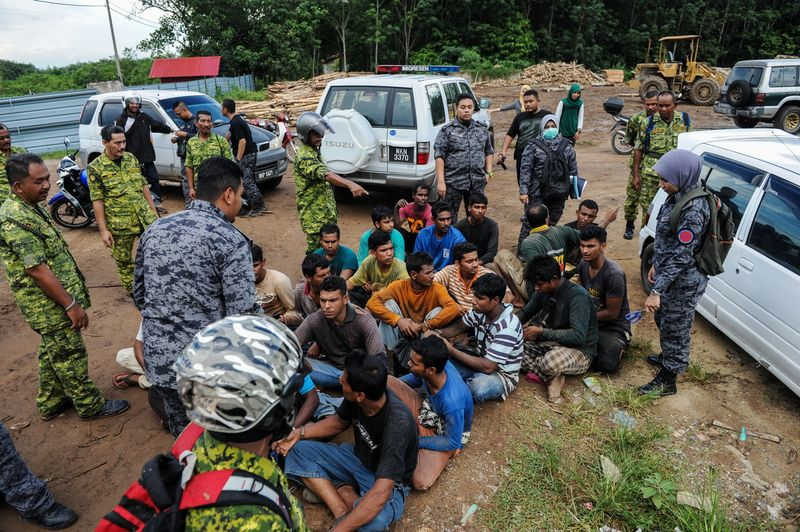 RELA and Immigration officers detaining illegal immigrants during a raid at a construction site in Kuala Nerang, July 5, 2017. — Bernama pic