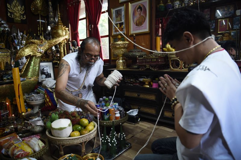 This photograph taken on May 20, 2017 shows 'hermit' Toon (left) preparing protective string before praying for his Taiwanese client at his home in the northern Thai province of Khon Kaen. — AFPpic