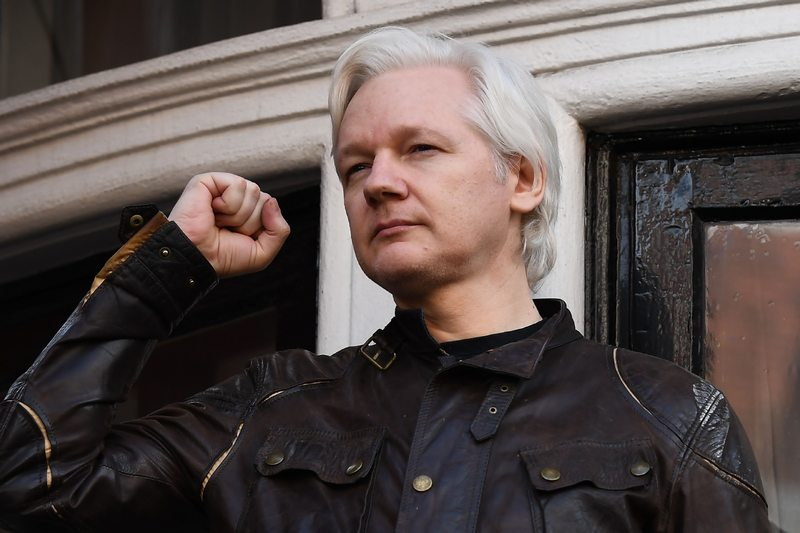 Wikileaks founder Julian Assange raises his fist prior to addressing the media on the balcony of the Embassy of Ecuador in London, May 19, 2017. — AFP pic