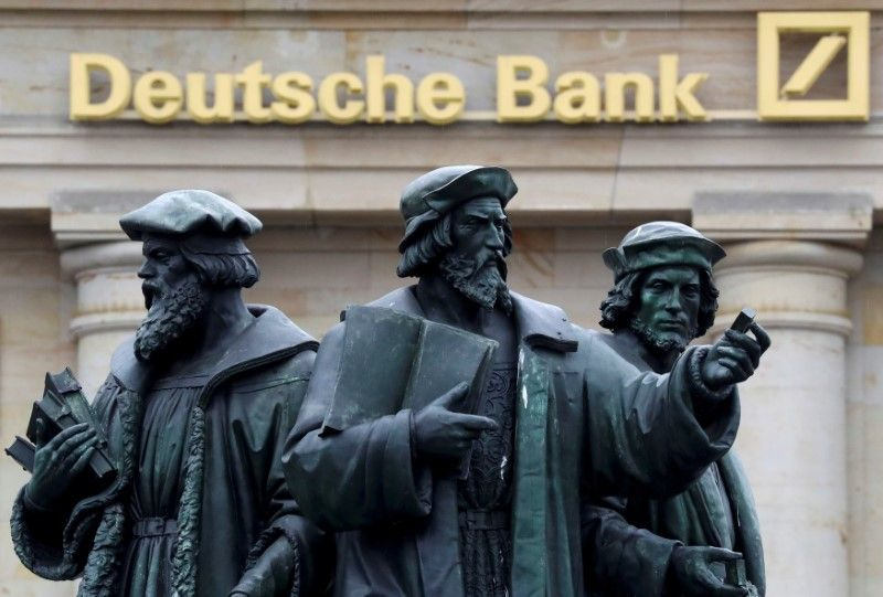 A statue is pictured next to the logo of Germany's Deutsche Bank in Frankfurt. — Reuters pic