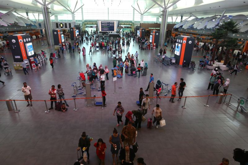 Travellers at KL International Airport. It is estimated over 800,000 people are trafficked internationally each year. — Picture by Zuraneeza Zulkifli
