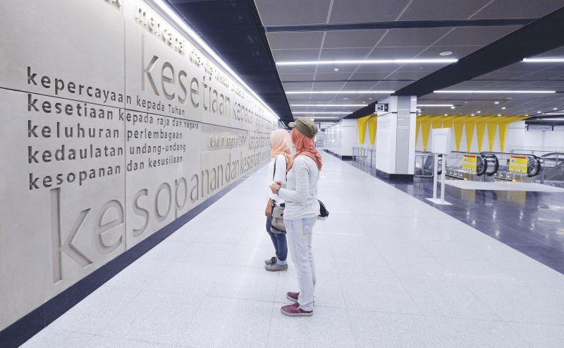 MRT users stop to admire the three-dimensional Rukunegara mural at the Merdeka MRT station. — Malay Mail pic