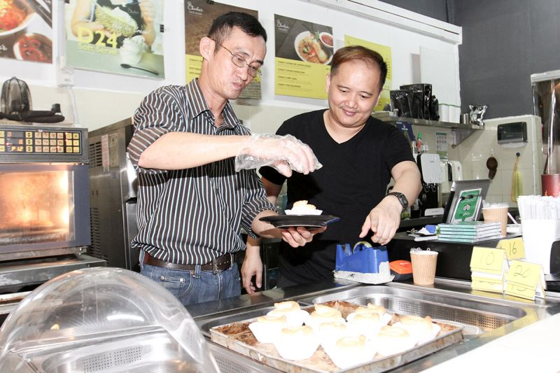 Ah Por (left) assisting Tuzan as kitchen helper and cook at Charlie's Cafe and Bakery in Taman Desa. — Picture by Miera Zulyana