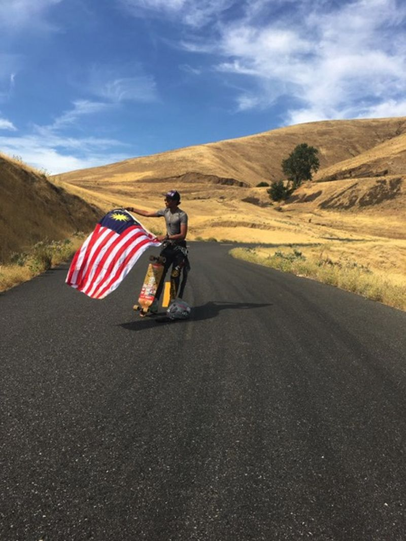 Jes, holding the Jalur Gemilang, leads a group of skate boarders downhill. ― Malay Mail pic