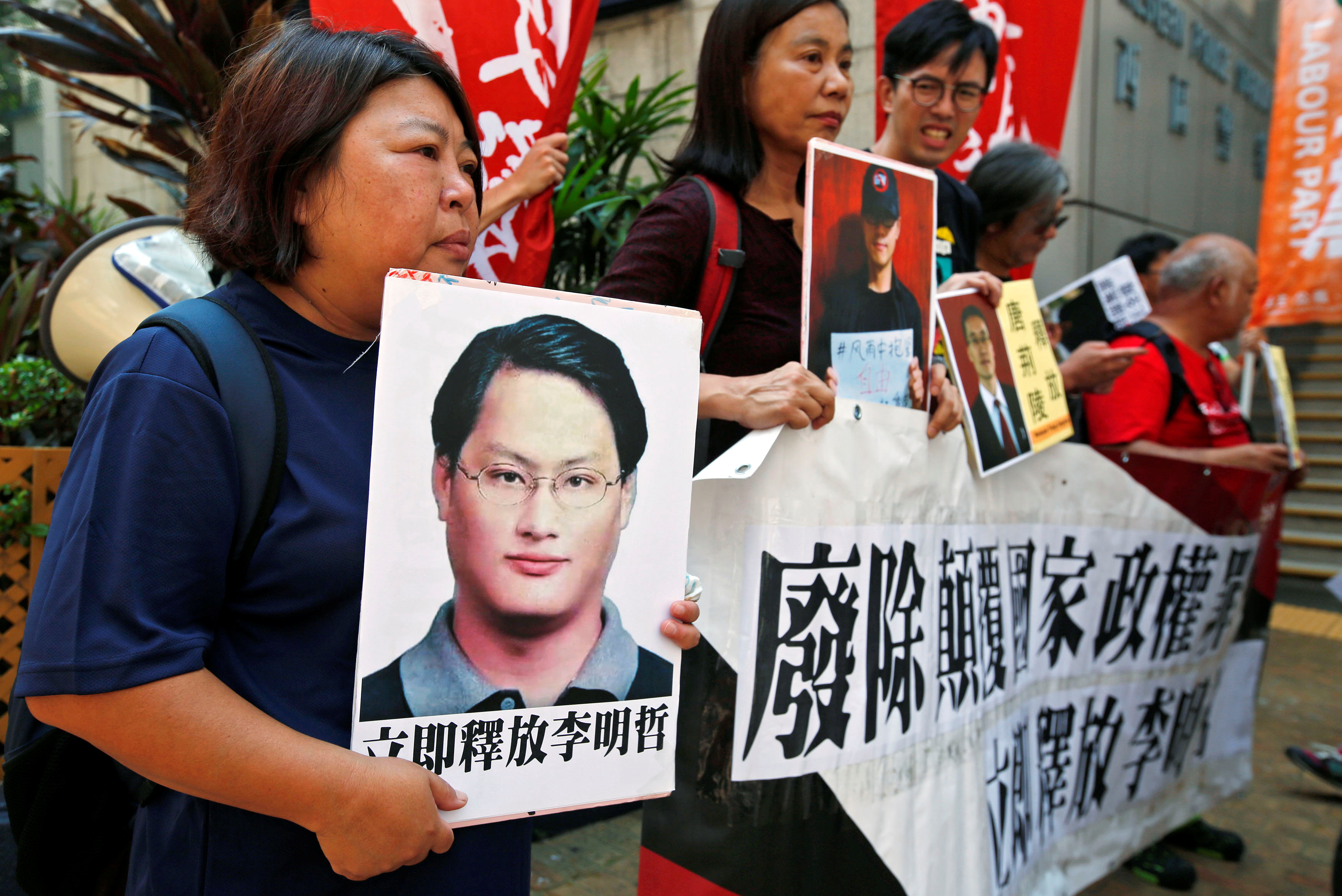 Pro-democracy protesters carry a photo of detained Taiwanese rights activist Li Ming-Che and other activists during a demonstration in Hong Kong, September 11, 2017. — Reuters pic