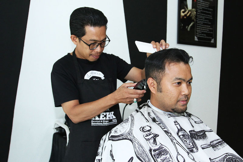 TN Winda Mohd Tahir, owner of BlackWhite Barbershop, attends to a customer.  — Picture by Miera Zulyana