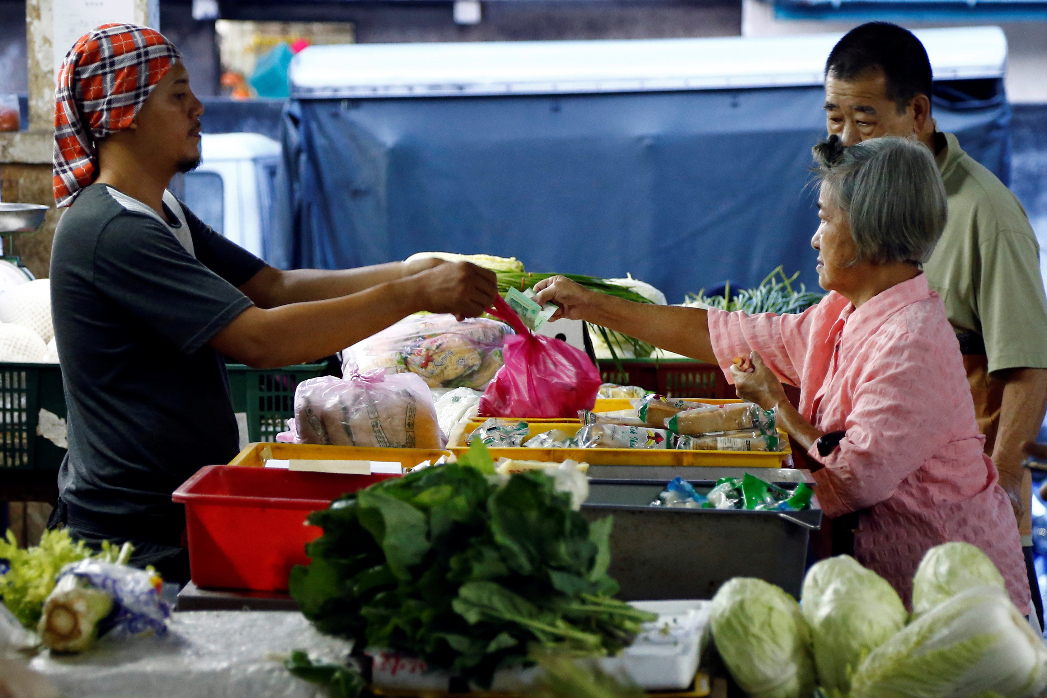 A customer pays for vegetables at a wet market in Klang, outside Kuala Lumpur. — Reuters pic