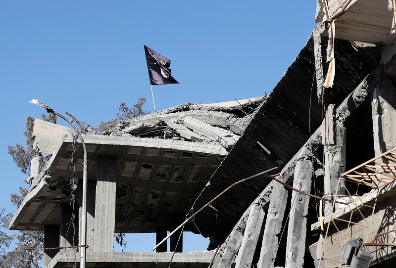 A flag of Islamic State militants is pictured above a destroyed house near the Clock Square in Raqqa, Syria October 18, 2017. — Reuters pic