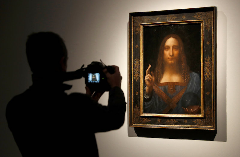 A member of Christie's staff takes a picture of Leonardo da Vinci's 'Salvator Mundi' painting in London October 24, 2017. — Reuters pic