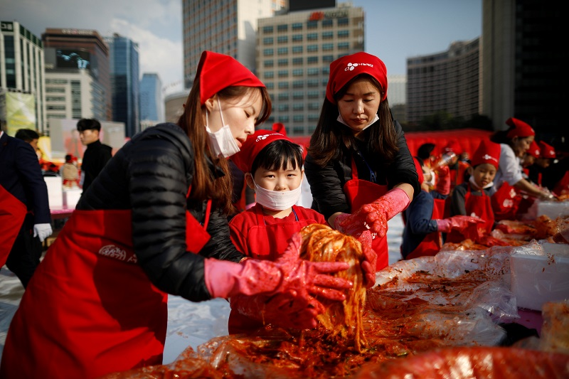 A boy makes traditional Korean side dish kimchi, or fermented cabbage, as he takes part in the Seoul Kimchi Festival in central Seoul November 3, 2017. — Reuters