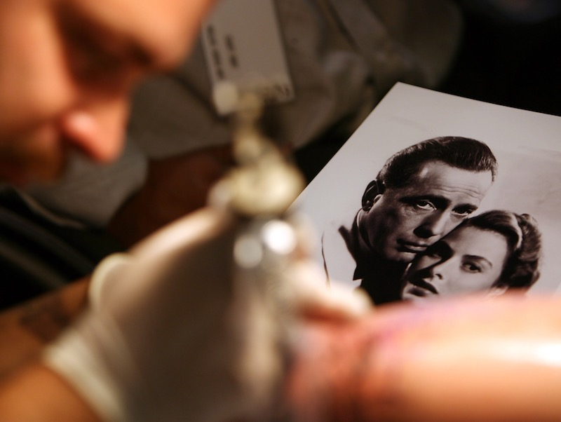This file photo taken on September 15, 2006 shows a tattoo artist working from a portrait of Hollywood legends Humphrey Bogart and Ingrid Bergman in Los Angeles. — AFP pic