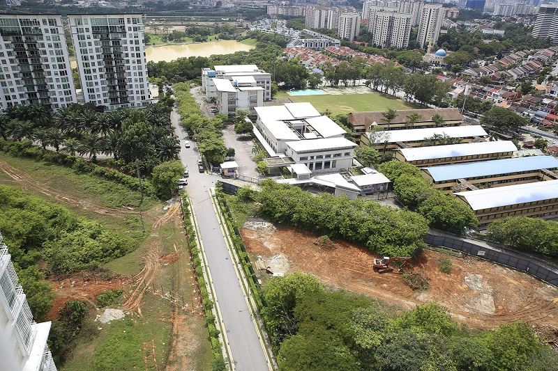 An aerial view of the project site where an excavator can be seen, with neighbouring schools and the 1Desa condominium also shown. — Picture by Yusof Mat Isa