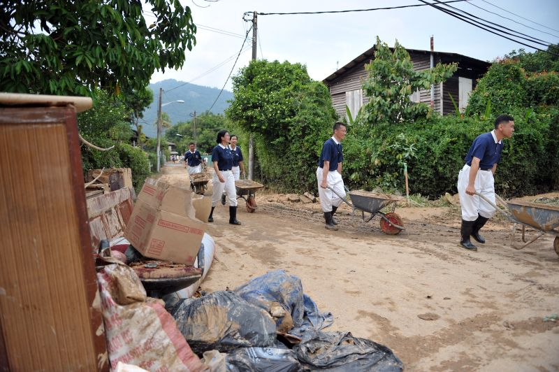 Tzu Chi Society volunteers helping to clear out mud at the Kampung Sheikh Madar.