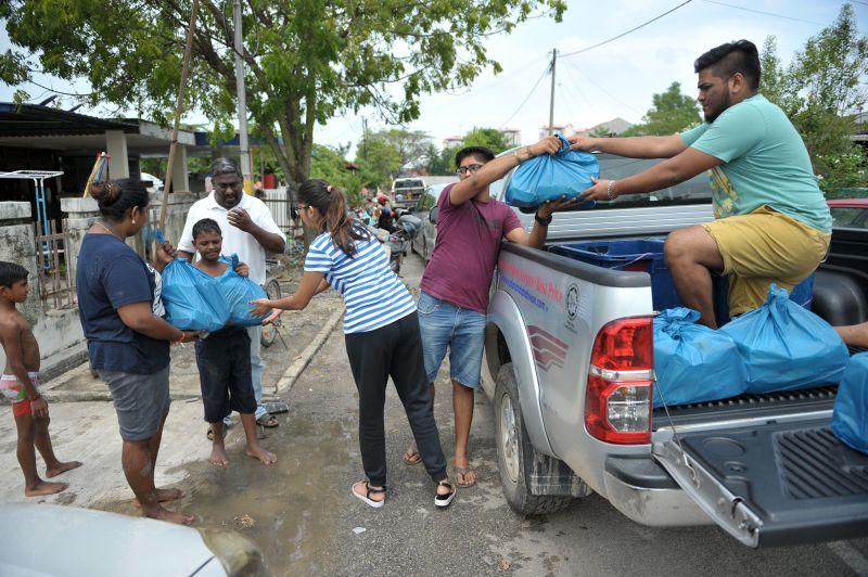 Volunteers of Amritesware Foundation handing out food at Taman Seri Rambai in Bukit Mertajam.