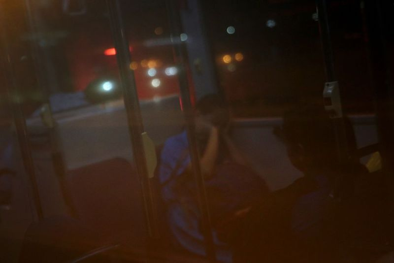 A student, seen reflected in a bus window, sleeps on board a bus, during a traffic jam along the Causeway, en route from Johor Bahru to Singapore in the morning on October 25, 2017. — TODAY pic