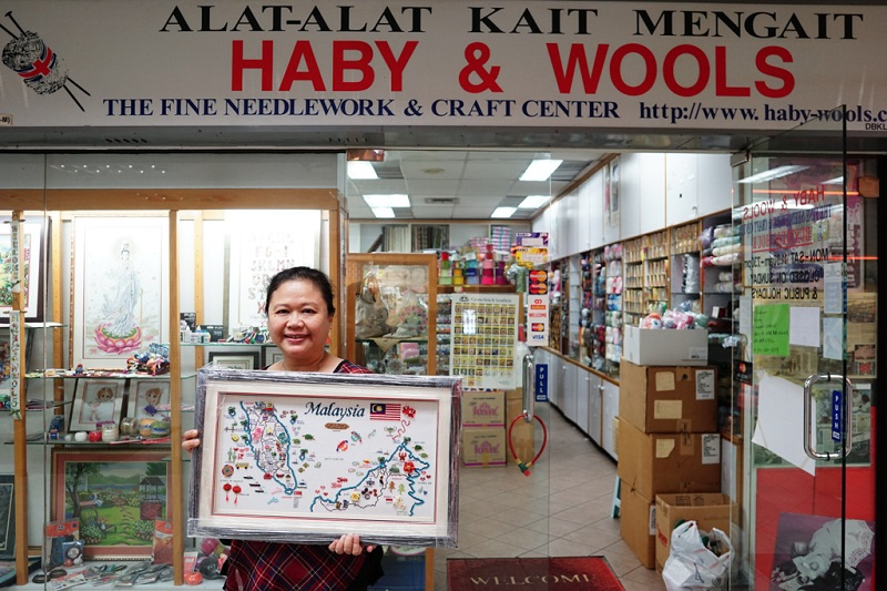Third generation owner of Haby & Wools Jenny Lee, 45, poses with one of her artworks in front of her shop in Ampang Park shopping centre in Kuala Lumpur.