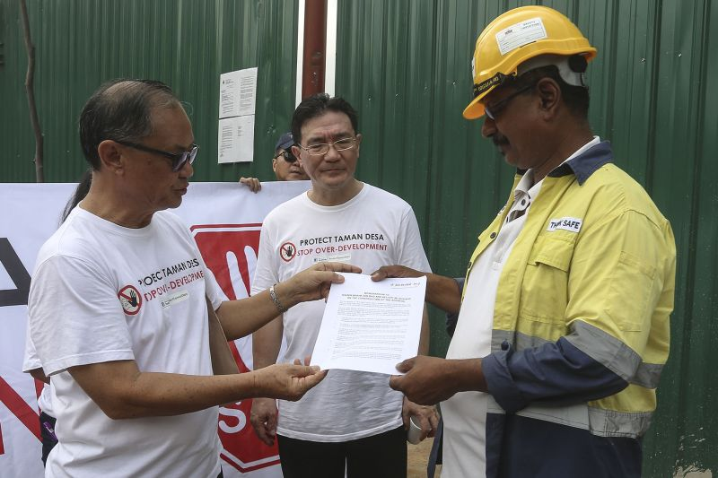 Tiara Faber resident KY Khong hands over a memorandum to contractor Keller (M) Sdn Bhd's site manager M. Chandiran as Protect Taman Desa coalition chairman Frank Yeh looks on. ― Picture by Yusof Mat Isa