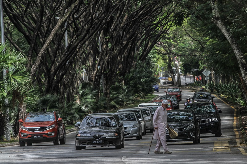 A pedestrians is seen crossing Jalan Datuk Sulaiman near the at-Taqwa mosque at Taman Tun Dr Ismail, Kuala Lumpur December 29, 2017. — Picture by Shafwan Zaidon