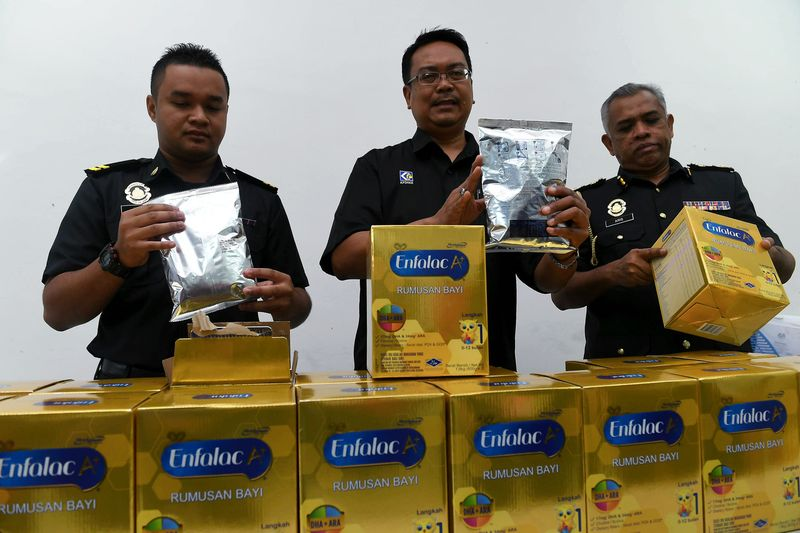 Johor Ministry of Domestic Trade, Cooperatives and Consumerism (KPDNKK) director Khairul Anwar Bachok (centre) showing confiscated infant formula, in Kulai, December 10, 2017. — Bernama pic