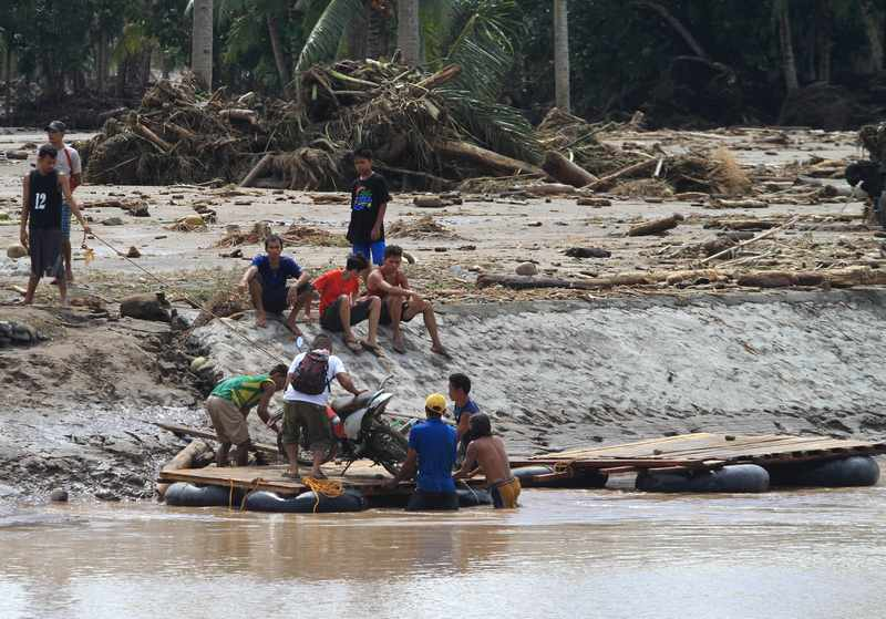 A man and his motorcycle are transported on a makeshift raft, after a bridge was destroyed by flash floods in Salvador, Lanao del Norte in southern Philippines December 23, 2017. — Reuters pic