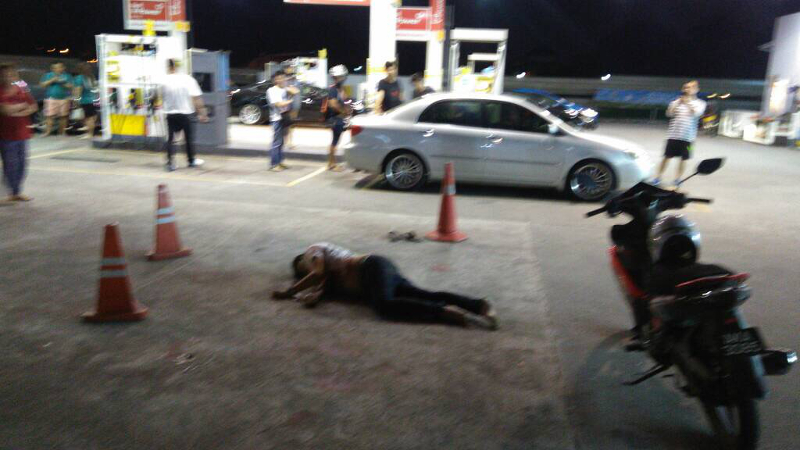 A male motorist lies unconscious at a Shell petrol station along Jalan Sri Pelangi in Taman Pelangi in Johor Baru after he was brutally attacked, stabbed and run over twice by his assailants tonight. — Picture courtesy of the police