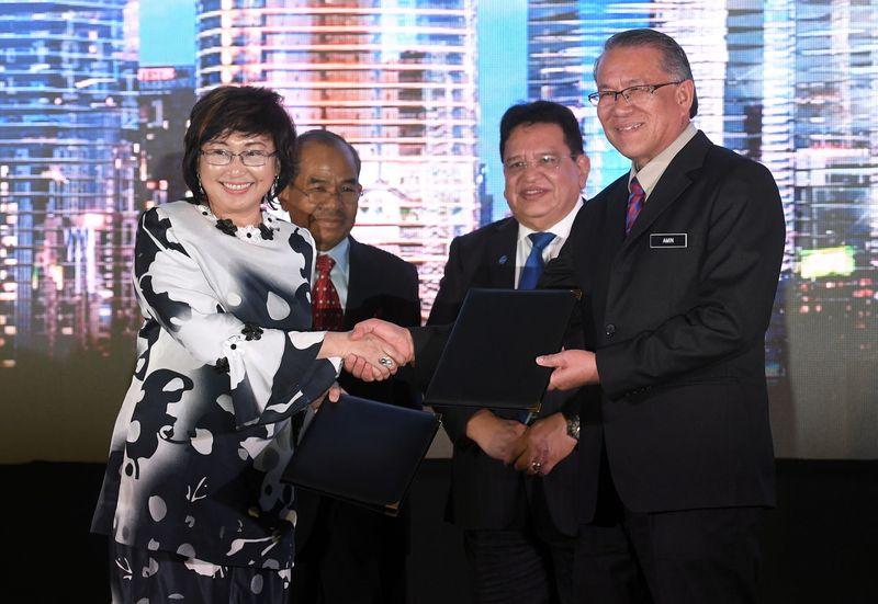Federal Territories Minister Datuk Seri Tengku Adnan Tengku Mansor (second right) and MDEC chairman Tan Sri Sidek Hassan witnessing the exchange of MoU between MDEC and DBKL, January 29, 2018. — Bernama pic