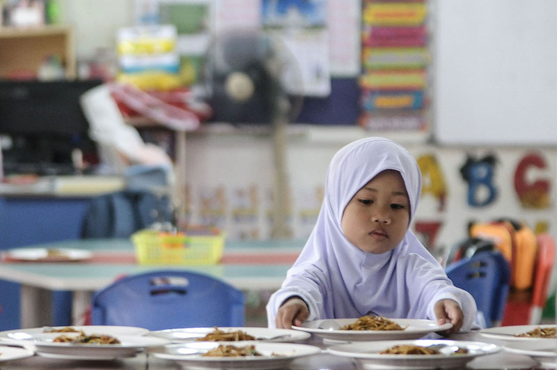 A preschool student eats breakfast on her first day of school in Puchong January 2, 2018. — Picture by Miera Zulyana