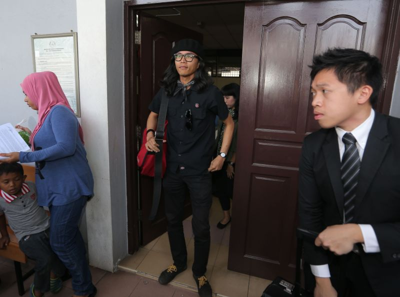 Fahmi Reza (centre) was charged for uploading false communication material on his Facebook page with the intention to offend other parties on February 8, 2016. ― Picture by Farhan Najib