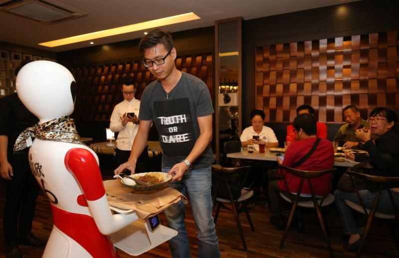 When the robot arrives at a table, customers will have to pick up their orders before touching the robot's hand to return it to the kitchen to pick up other orders. — Picture by Marcus Pheong