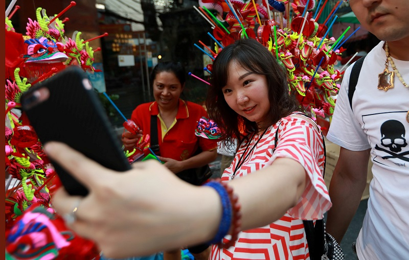 A Chinese tourist takes a selfie photo as she buys Chinese traditional dragon toys in Chinatwon in Bangkok February 16, 2018. — Reuters pic