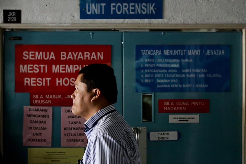 An Indonesian Consulate member waits to claim the body of Indonesian maid Adelina Lisao in Seberang Jaya Hospital in Perai February 11, 2018. — Picture by Sayuti Zainudin