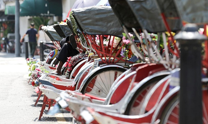 A trishaw paddler rests under the shade of his trishaw at Lebuh Penang in George Town February 19, 2018. — Picture by Sayuti Zainudin
