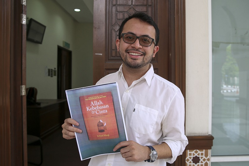 Mohd Ezra Mohd Zaid holds a picture of the Bahasa Malaysia translation of Irshad Manji's book 'Allah, Love and Liberty' outside the courtroom at the Shariah Subordinate Court in Petaling Jaya on February 22, 2018. — Picture by Yusof Mat Isa