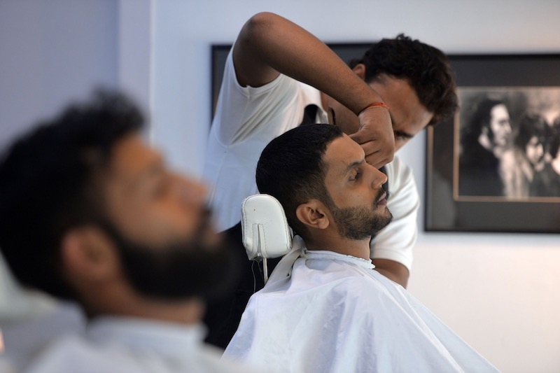 This photograph taken on October 10, 2017 shows a male hairdresser cutting the hair of a customer at a men's salon in Islamabad. — AFP pic
