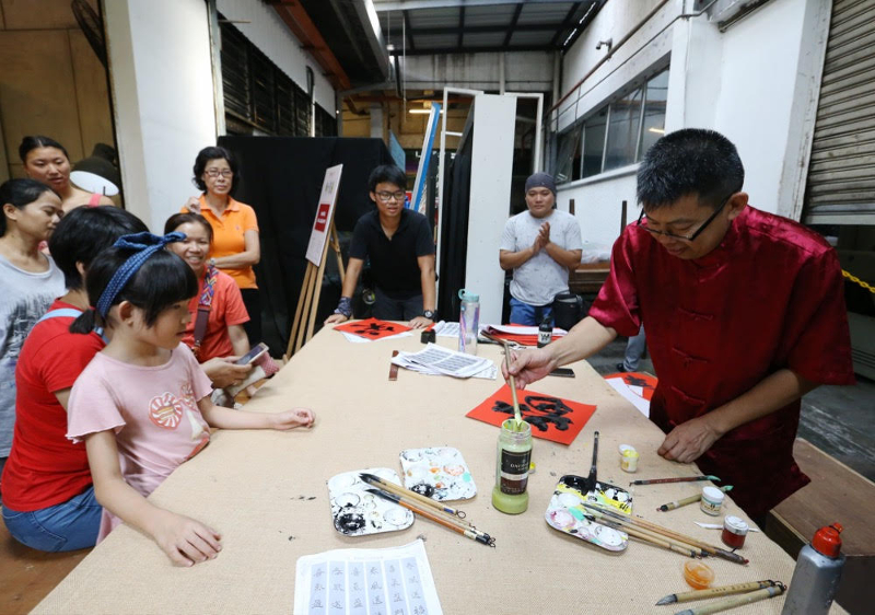 Eight-year-old Elisha Zou (left) watches as calligrapher Lai Choong Sheong demonstrates Chinese calligraphy at a workshop at Gong Xi RIUH in Bangsar February 11, 2018.