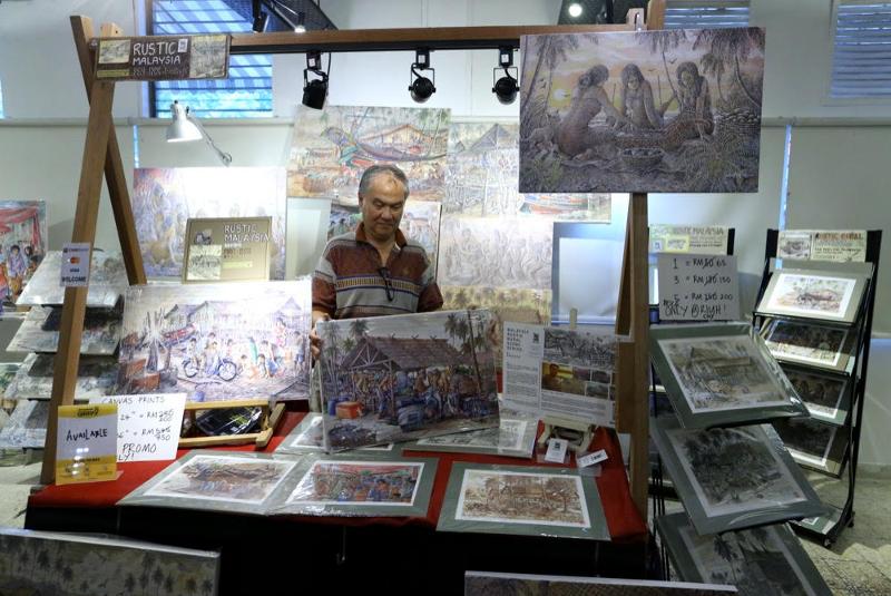 Malaysian artist Rashidtop, 67, arranges his artworks at the Rustic Malaysia popup store at Gong Xi RIUH in Bangsar February 11, 2018.