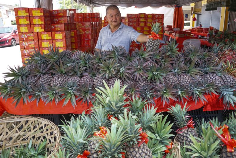 A fruit vendor sells pineapples for the Chinese New Year celebrations in Ipoh February 10, 2018. ― Picture by Ahmad Zamzahuri
