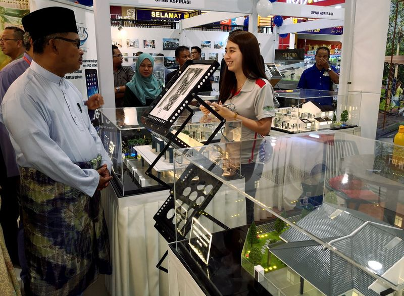 Melaka Chief Minister Datuk Seri Idris Haron (left) looking at scale models of commercial buildings displayed by property developers after launching Melaka State Housing and Special Property Expo 2018 at Mydin Ayer Keroh, February 2, 2018. — Bernama pic