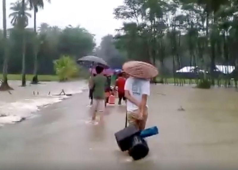 Residents walk through flooded rice fields in Cantilan, Surigao Del Sur province, Philippines February 13, 2018 in this still image obtained from social media video. — Reuters pic