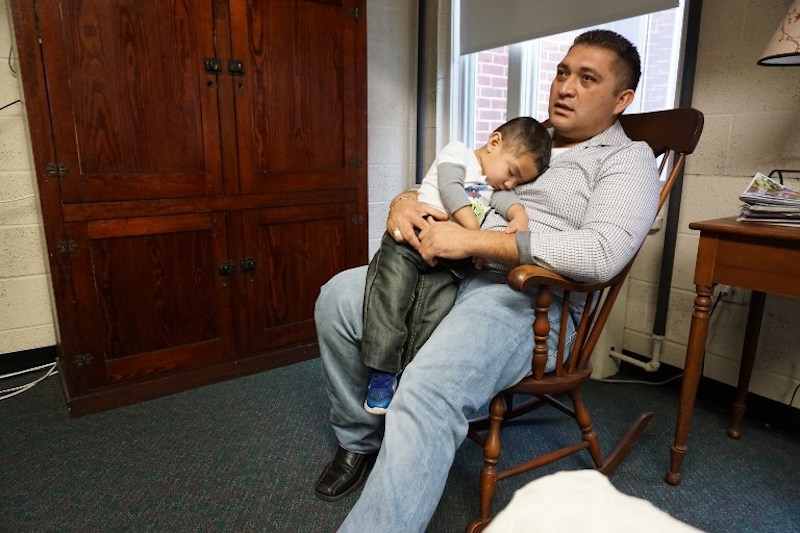 Business owner Oscar Canales holds his son, George, as he speaks during an interview at the Congregational United Church of Christ where he is living in sanctuary in Greensboro, North Carolina February 12, 2018. — AFP pic