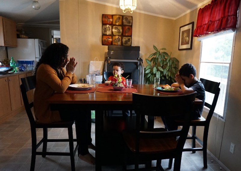 Minerva Cisneros Garcia prays with her sons, Mateo and Antonio, before eating at their home in Winston-Salem, North Carolina, February 12, 2018. — AFP pic