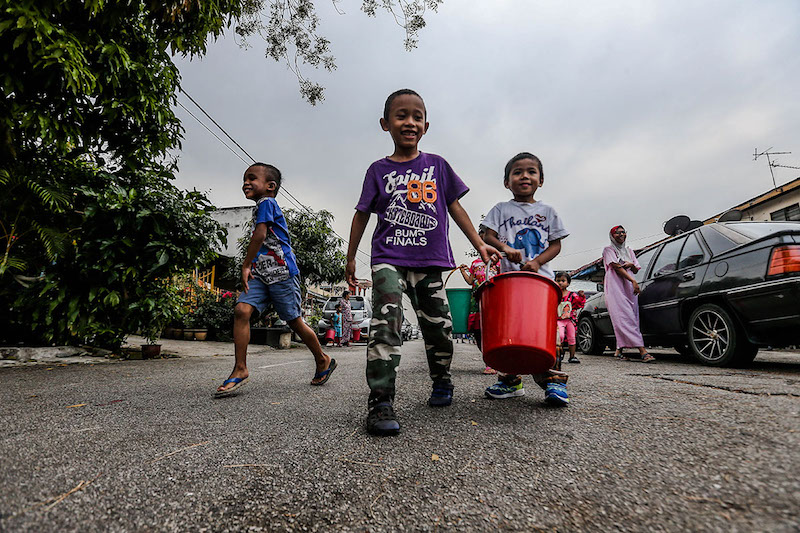 Children from Taman Tasek Tambahan in Ampang head to the water tanker to fill up pails with water following the water disruption in the Klang Valley, March 6, 2018.  — Picture by Hari Anggara
