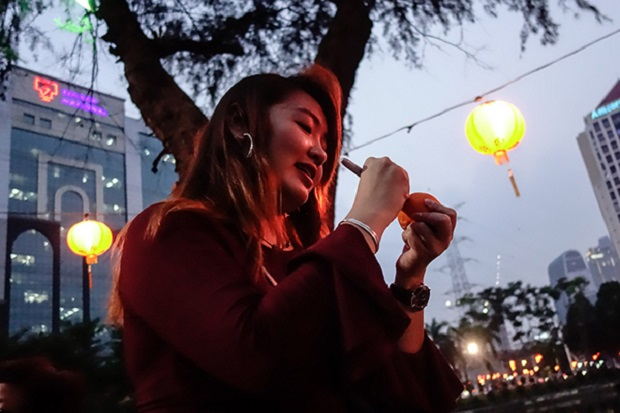 Accounting student Chin carefully writes her name and contact information on a mandarin orange before tossing it into the Taman Jaya lake in Petaling Jaya March 2, 2018.
