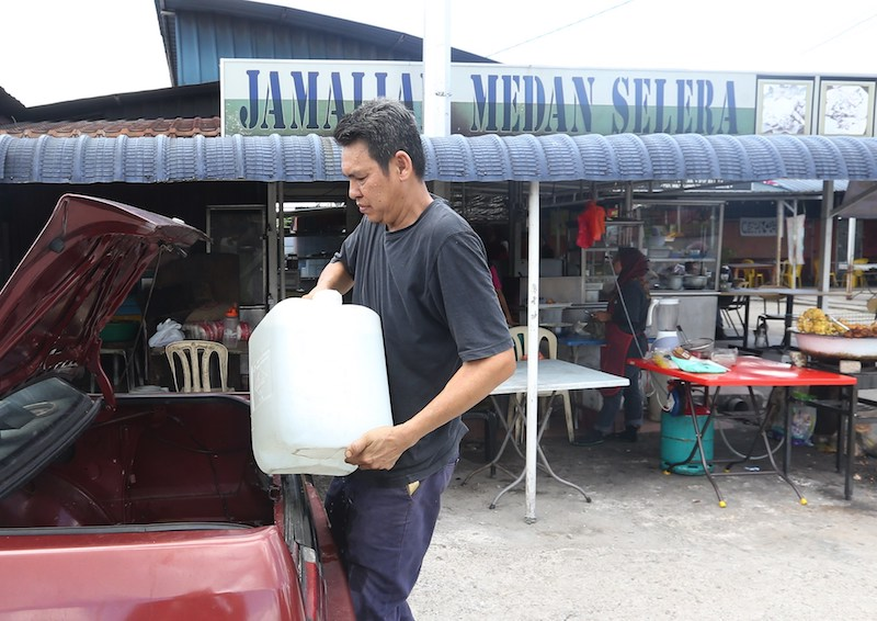 Satay stall owner Iles Jusoh unloads a water container from his car in Ampang March 8, 2018. — Picture Razak Ghazali