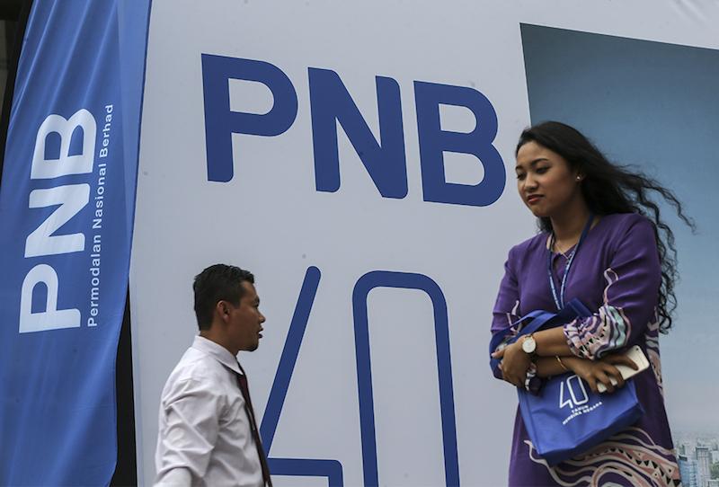 People walk past a Permodalan Nasional Bhd (PNB) logo in Kuala Lumpur March 15, 2018. — Picture by Azneal Ishak