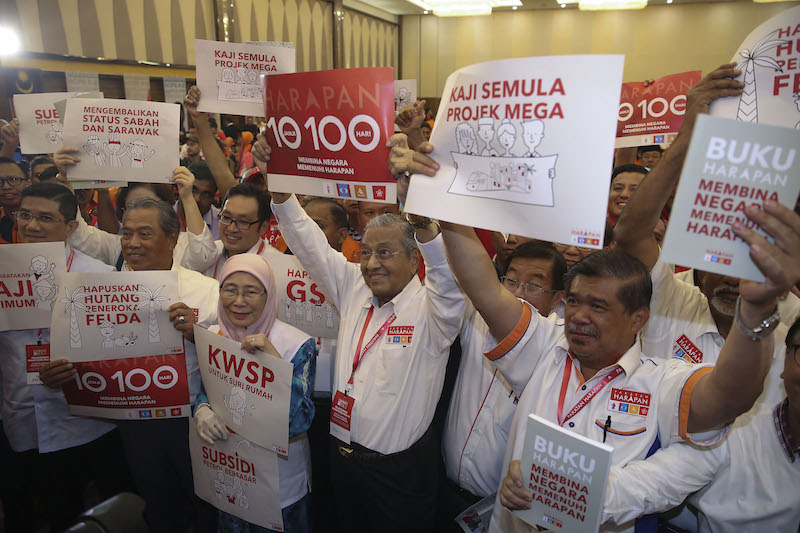 Pakatan Harapan leaders pose for photos while holding banners with manifesto pledges after the launch of Buku Harapan in Shah Alam March 8, 2018.