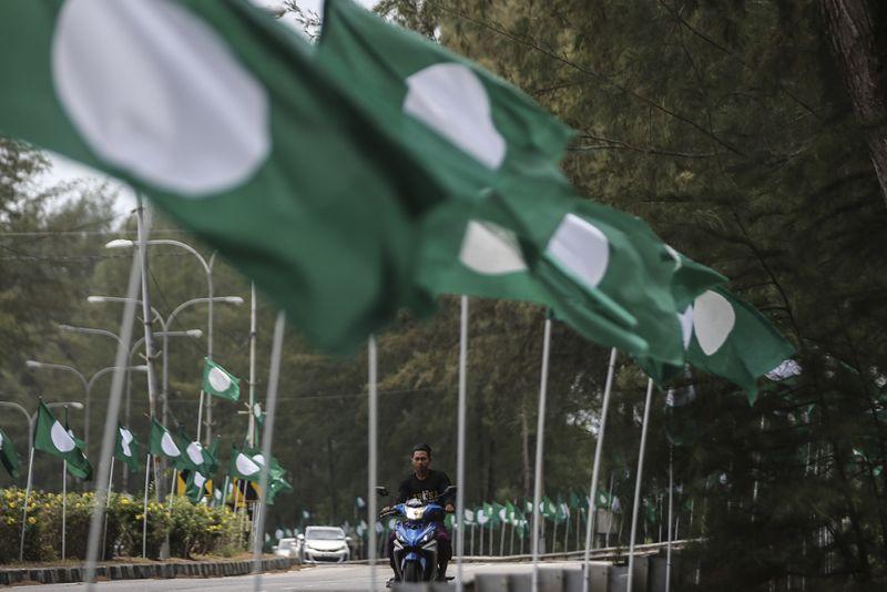 A motorcyclist rides past PAS and Barisan Nasional flags along Jalan Batu Buruk in Kuala Terengganu March 23, 2018. ― Picture by Azneal Ishak